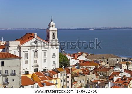 Alfama District with Santo Estevao Church and the Tagus River estuary seen from Miradouro de Santa Luzia. Lisbon, Portugal. - stock photo