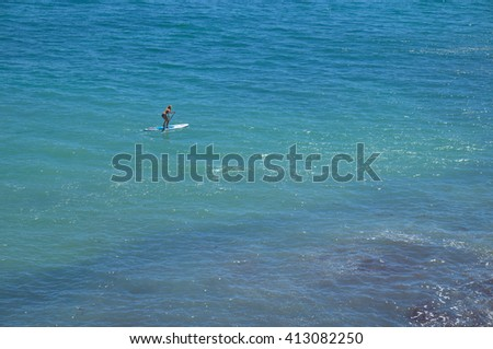 ALGARVE, PORTUGAL - April 24, 2016: Woman practicing Paddleboard in Albandeira beach in Lagoa, a popular beach among tourists during summer season . Travel and vacation destinations.