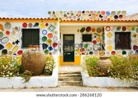 ALGARVE, PORTUGAL - MAY 3, 2015: Traditional colorful ceramic plates on the wall of the local pottery shop.  Algarve is famous for its hand-painted pottery and ceramics.  - stock photo