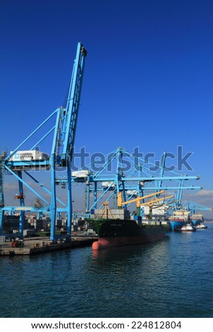ALGECIRAS, SPAIN - DECEMBER 24: Container ship being loaded in the Mediterranean port of Algeciras, the 6th busiest container port in Europe. On December 24, 2013 in Algeciras, Spain. - stock photo