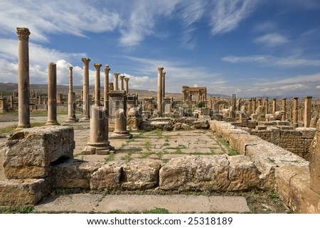 Algeria. Timgad (ancient Thamugadi or Thamugas). Row of columns at the forum and colonnade along Decumanus Maximus street terminated Trajan's Arch - stock photo