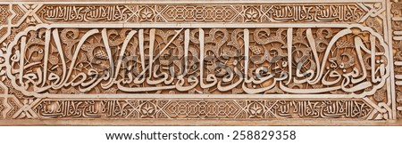 Alhambra de Granada. Arabic plasterwork text detail in Nasrid Palaces - stock photo