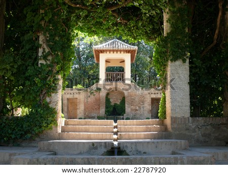 Alhambra gardens - streams, towers, lush vegetation (Grenada, Spain) - stock photo