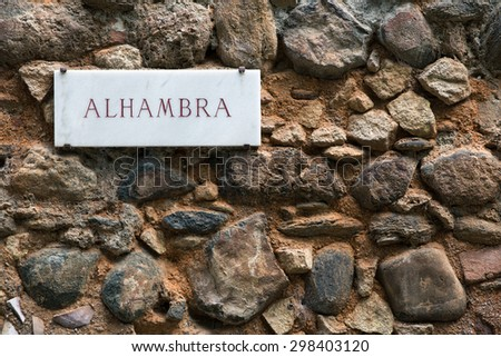 Alhambra sign on ancient wall - stock photo