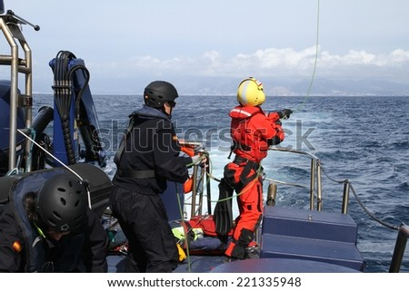 ALICANTE COAST, SPAIN - JULY 6: The helicopter of the Spanish  Maritime Rescue Team and his rescuers training over the deck of a coast guard ship, on july 6, 2014 in Alicante coast. - stock photo