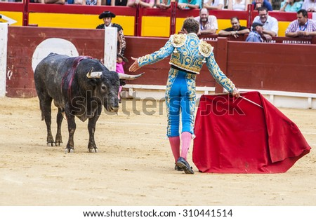 "ALICANTE / SPAIN, AUGUST 2015: Spanish torero is performing a bullfight at the bullfight arena on august, 2010 in Alicante (Spain). ""Corrida"" (bullfighting) of bulls is Spanish tradition."