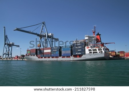 """ALICANTE, SPAIN  JULY 12: The container cargo vessel """"RENATE P"""" is docked in the port of Alicante working with containers crane, on July 12, 2014 in Alicante. - stock photo"""
