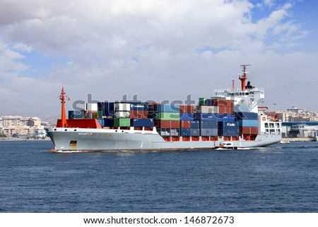 "ALICANTE, SPAIN � JULY 20: The container cargo vessel ""RENATE P"" is leaving the port of Alicante helped with tugs and the pilot cutter, on July 20, 2013 in Alicante."