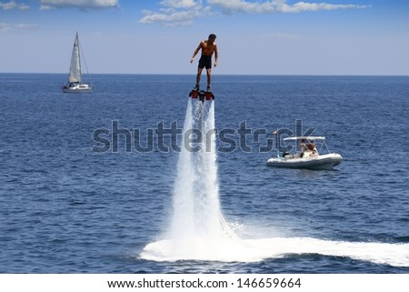 ALICANTE, SPAIN - JULY 10: The new spectacular sport, the flyboard is showed in the coast of Alicante beach; on july 10, 2013 in Alicante. - stock photo