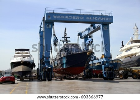 ALICANTE, SPAIN. MARCH 06: Travelift carrying coast guard ship in place in shipyard for repairs and maintenance; on march 06, 2017 in Spain.