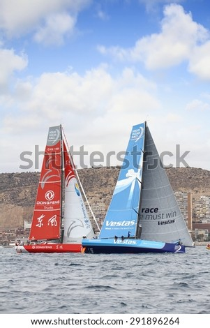 """ALICANTE, SPAIN - OCTOBER 04: The sail boat of the Team Vestas Wind and Dongfeng are sailing in the """"Volvo Ocean Race 2014-2015"""" in-port race in Alicante bay, on october 04, 2014 in Alicante. - stock photo"""