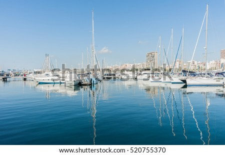 ALICANTE, SPAIN - SEPTEMBER 9; Marina and luxury boats yacht masts reflected in calm turquoise water with city skyline behind September 9, 2016,  Alicante, Spain