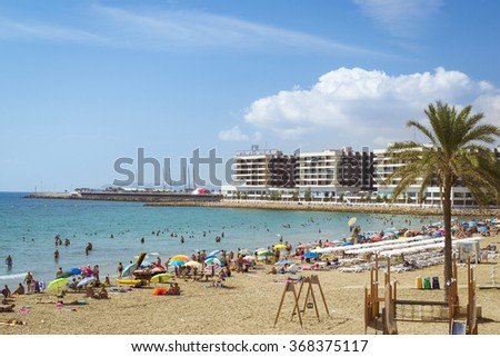 ALICANTE, SPAIN - SEPTEMBER 9, 2014: Sunny beach Playa del Postiguet near the castle Santa Barbara. Tourists relax under umbrellas on the warm sand. Alicante, Valencian Community, Spain