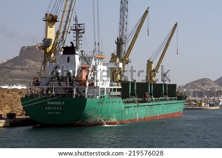 "ALICANTE, SPAIN - SEPTEMBER 05: The general cargo vessel ""SUNROSE E"" is working with cranes to tree bark in the port of Alicante; on september 05, 2014 in Alicante."