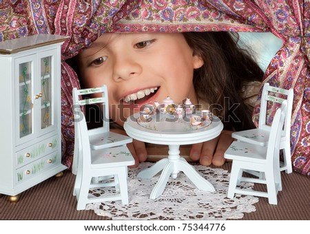 Alice in wonderland looking into a dollhouse - stock photo