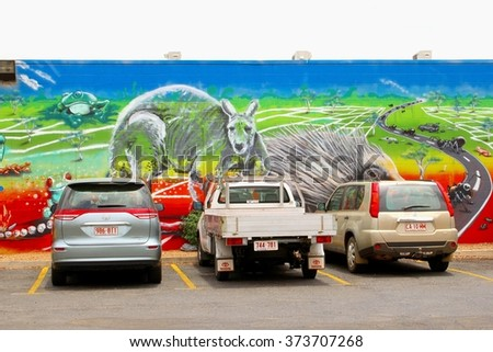 ALICE SPRINGS, AUSTRALIA  - December 6. Car parking along a wildlife street art wall painting with a landscape, kangaroo, porcupine and insects on December 6, 2015 in Alice Springs.  - stock photo