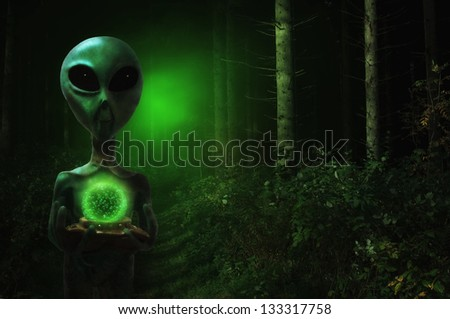 Alien in a forest holding a glowing orb - stock photo