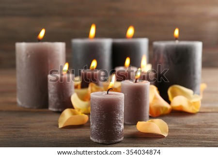 Alight wax grey candle with flower petals on wooden background - stock photo