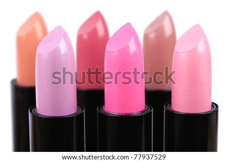 Align lipsticks different colors, closeup on white