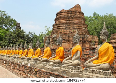 Aligned buddha statues with orange bands in Ayutthaya, Thailand - stock photo
