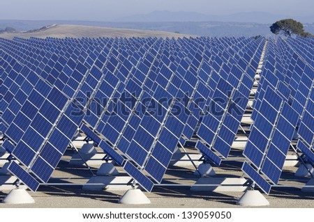 aligned group of photovoltaic panels for renewable electric energy production - stock photo