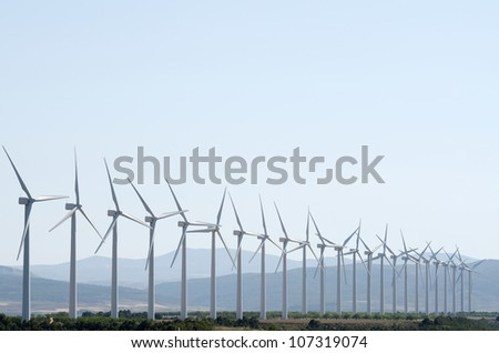 aligned group of windmills for renewable electric energy production, Cintruenigo, Navarre, Spain - stock photo