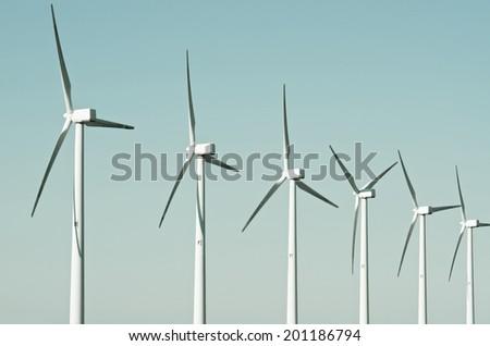 aligned group of windmills for renewable electric energy production, Cintruenigo, Navarre, Spain - stock photo