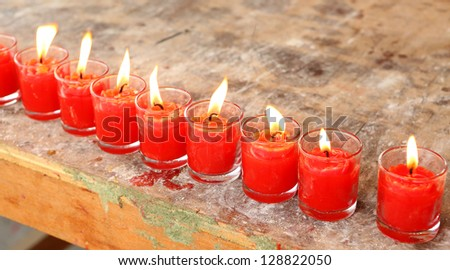 aligned Red candles burning in glass