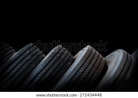 alignment of car tires in black background, used tires - stock photo