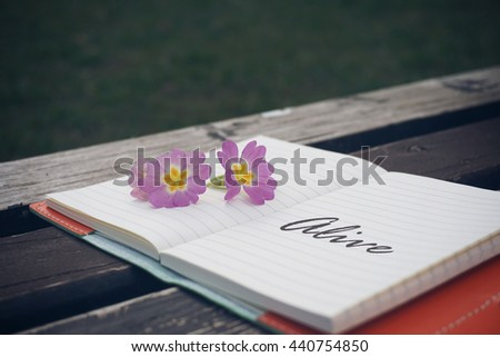Alive text on open notebook with flower on wooden table - stock photo