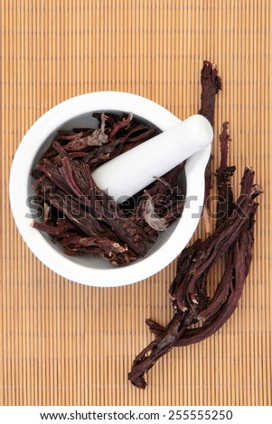 Alkanet herb root in a porcelain mortar with pestle and loose over bamboo background. Alkanna tinctoria. - stock photo