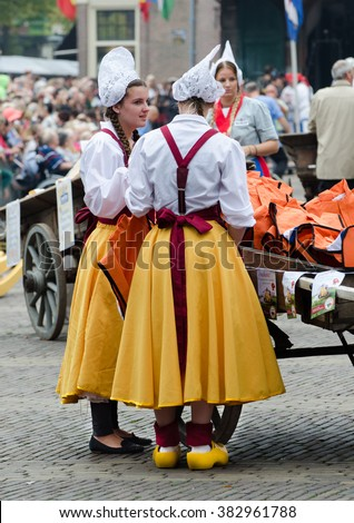 ALKMAAR, HOLLAND, THE NETHERLANDS - SEPTEMBER 5, 2014: Girls in Traditional Dutch dress work at the Alkmaar cheese market,  Netherlands