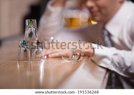 All Alone.  Man drowning in his sorrows drinking whiskey by himself at a bar.  - stock photo