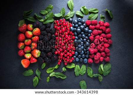 All berries fresh, from farm or forest with mint leafs on dark slate background - stock photo