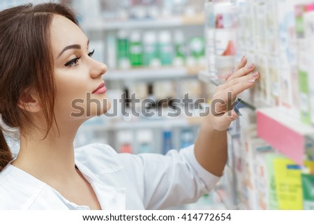 All checked. Shot of a young joyful female pharmacist checking the stock at the local drugstore. - stock photo