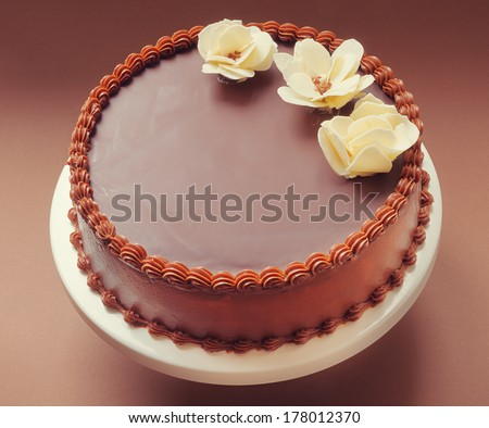 All chocolate birthday cake, on brown background, decorated with yellow flowers on top.  - stock photo