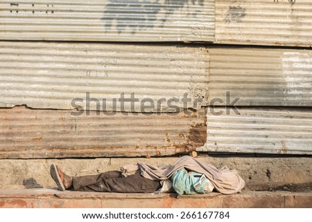 all cover dirty tramp man sleep in outdoor and sunlight at chandni chowk, Delhi, India - stock photo