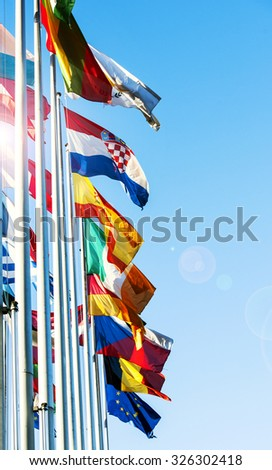 All EU members flags waving in front of the European Parliament building in Strasbourg, France - vertical shot with beautiful sun flare - stock photo