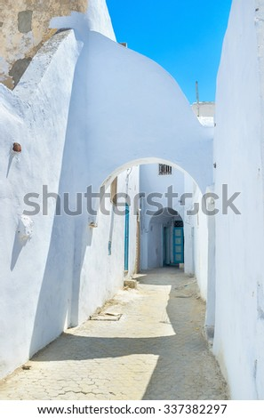 All houses in the old neighborhoods in Median are white with the tine arches on the narrow streets, Kairouan, Tunisia.