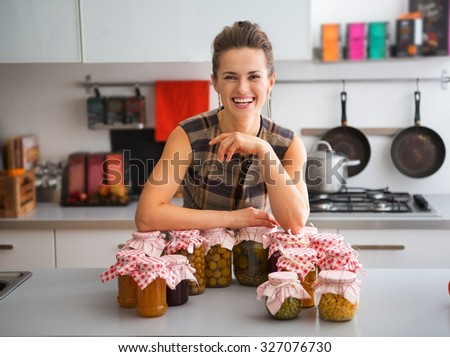 All in a day's work... This happy, smiling and elegant woman is so proud of all she has accomplished today in preserving seasonal fruits and vegetables to enjoy later in the year. - stock photo