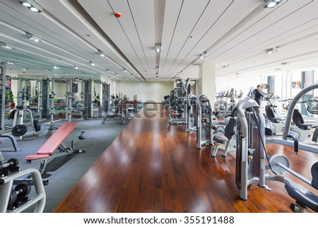 all kinds of fitness apparatus in modern gym - stock photo