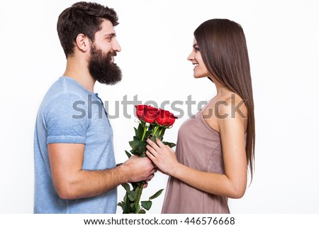 All my love for you. Close-up portrait of beautiful young couple holding bouquet of roses and smiling while looking on each other while isolated on white.