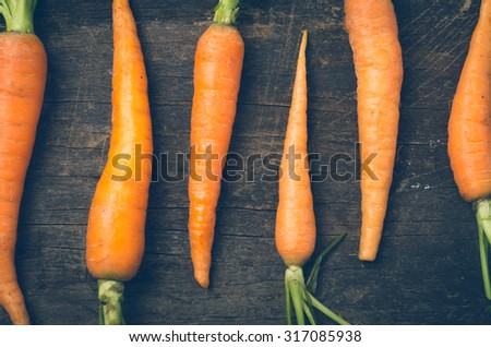 all-natural carrots lined up on wooden board rustic concept. - stock photo