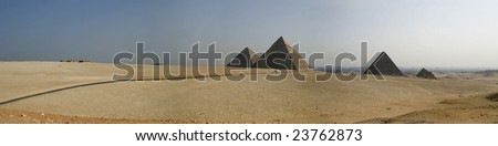 all of the great pyramids on the giza plateau, with a smoggy cairo behind them.