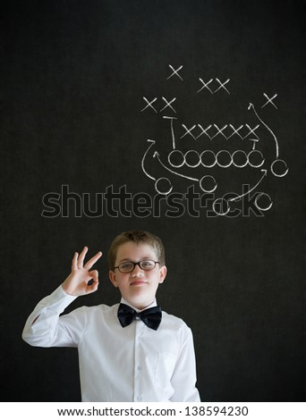 All ok or okay sign boy dressed up as business man with chalk American football strategy on blackboard background - stock photo