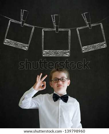 All ok or okay sign boy dressed up as business man with hanging instant photograph on blackboard background - stock photo