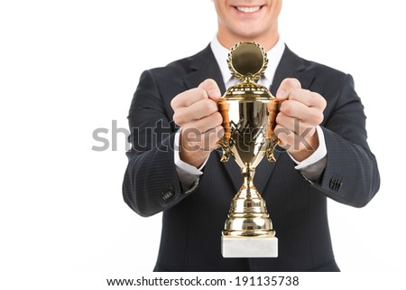 All-round champion. Business man holding a gold Trophy - stock photo