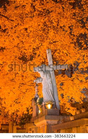 All saints day - figure of Jesus with cross illuminated by the grave candles, Krakow, Poland