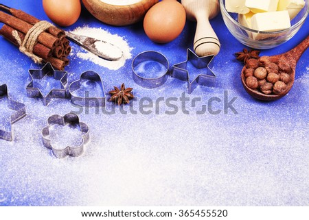 All stuff and ingredients for making cookies or gingerbread, lying on blue surface with flour and place for text on it. Baking with love concept. - stock photo