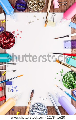 All the decorating and painting. White sheet of paper, surrounded by tools for drawing and dotted with decorative stars. - stock photo